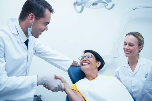 patient sititng in a dentist chair while shaking hands with the dentist